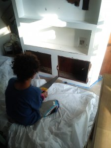 Boy using saw in camper renovation