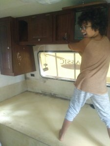Young child using hammer to smash cabinet in RV renovation